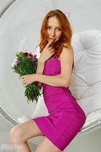 Irresistible doll with exceptional features and a beautiful face in high heels spreading her thin legs in a white seat with flowers.